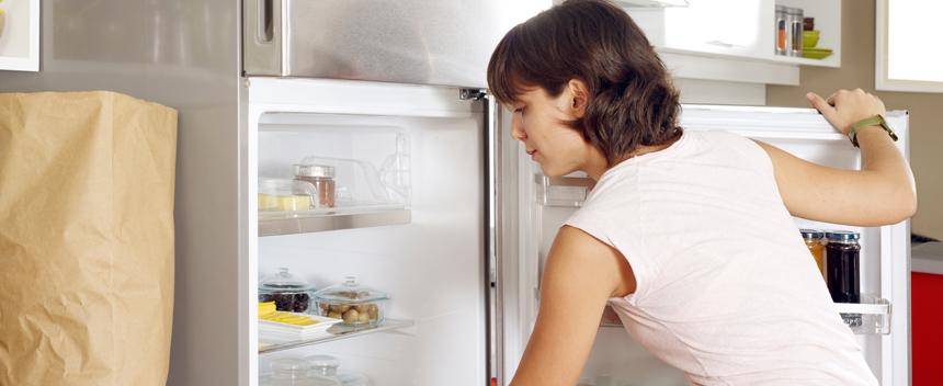 Dame som åpner kjøleskap