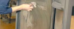 Hånd som vasker glasset på en peisovn