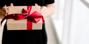 svart jul - dame i svart kjole gir presang